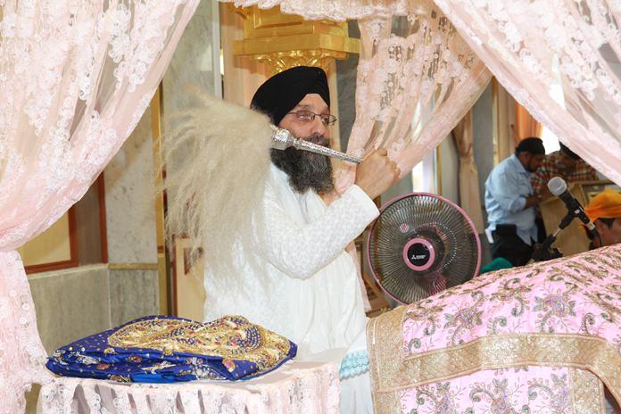Gianiji Deep Singh waves the Chaur Sahib (ceremonial whisk) over the sacred Guru Granth Sahib.