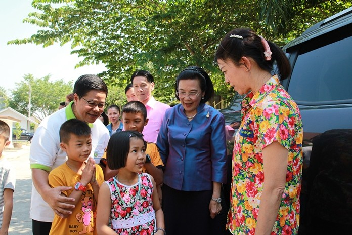 Children, along with center and government officials, walk Supaporn out to her awaiting van to say goodbye and thank her for a wonderful day.