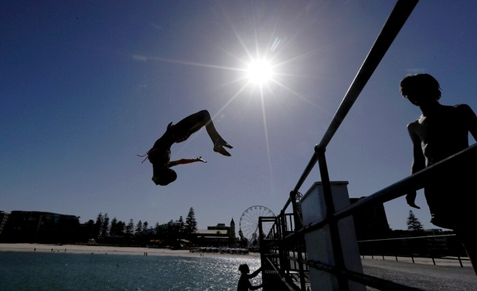 In this Jan. 24, 2019, photo, a beachgoer jumps off a jetty at Glenelg Beach in Adelaide, Australia, as temperatures climb to 45 Celsius (113 ‎Fahrenheit). (Kelly Barnes/AAP Image via AP)