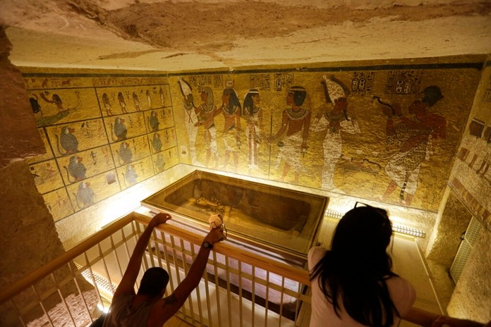 In this Thursday, Nov. 5, 2015, file photo, tourists look at the tomb of Egypt's famed boy pharaoh Tutankhamun, displayed in a glass case in the Valley of the Kings, located on the west bank of the Nile River in Luxor, Egypt. (AP Photo/Amr Nabil)