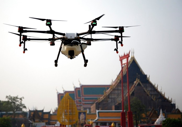 A water-spraying drone is flown over the Suthat Temple in Bangkok, Thursday, Jan. 31. (AP Photo/Sakchai Lalit)