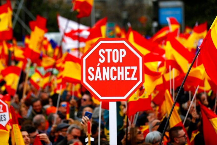 Demonstrators hold banners and Spanish flags during a protest in Madrid, Spain, on Sunday, Feb.10. (AP Photo/Andrea Comas)