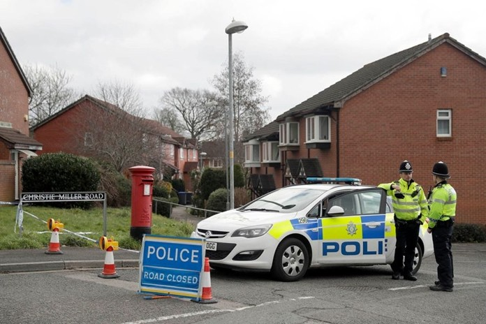 In this Tuesday, March 13, 2018 file photo, police officers stand guard at the bottom of the road where poisoned former Russian double agent Sergei Skripal lives in Salisbury, England. (AP Photo/Matt Dunham)