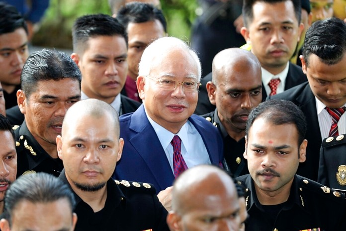 In this July 4, 2018, file photo, former Malaysian Prime Minister Najib Razak, center, arrives at a court house in Kuala Lumpur. (AP Photo/Vincent Thian)