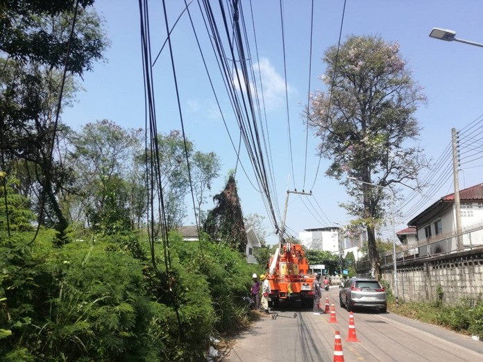 Workers from the Provincial Electricity Authority organize low-hanging utility wires on Soi Paniadchang.
