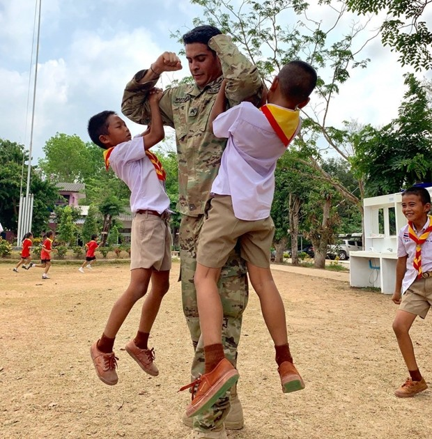 Sgt. Antonio Martinez, US Army reservist assigned to the 416th Civil Affairs Battalion (Airborne), plays with two Thai school children at Ban Wang Mai Daeng School during Cobra Gold 19. (U.S. Navy photo by Lieutenant Junior Grade Travis Weger)