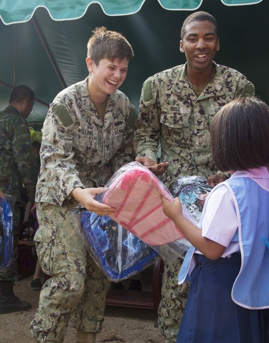 U.S. Navy Petty Officer 3rd Class Autumn Williams, Left, and Petty Officer 3rd Class Jamarcus Bell, Right, help hand out backpacks to the students from the Ban Man Kroi School during exercise Cobra Gold 19 at Ban Man Kroi School, Rayong. Williams, a native of Poca, West Virginia and Bell, a native of Orlando, Florida are builders with Naval Mobile Construction Battalion 3. (U.S. Marine Corps photo by Lance Cpl. Kenny Nunez.)