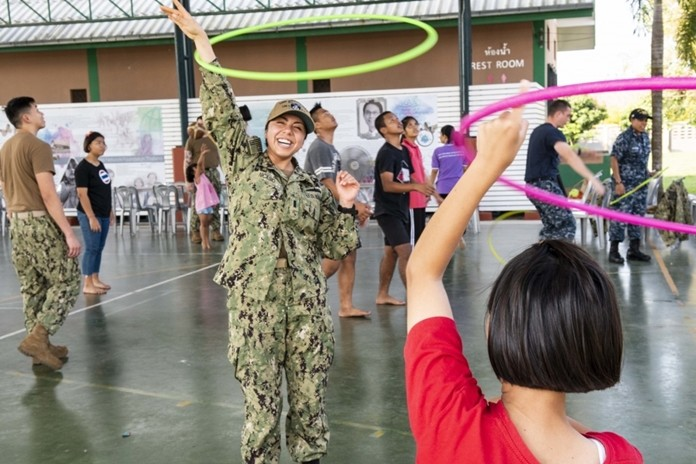 Lt. j.g. Jasmin Nicasio, from San Diego, hula hoops with a child during a community service project at the Child Protection and Development Center in Chonburi.