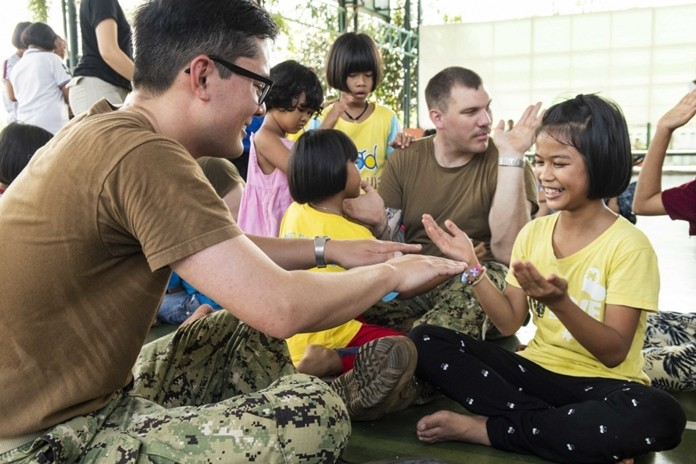 Lt. Mick Radiou, from Staunton, Va., and Gunner's Mate 2nd Class Dylan McCurry, from Antioch, Ill., play games with children during a community service project at the Child Protection and Development Center in Chonburi.