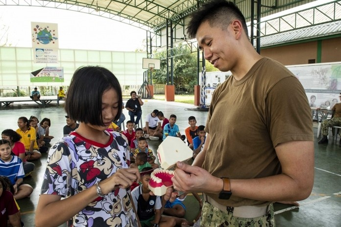 Lt. Michael Siy, from Fresno, Calif., quizzes a child on good oral hygiene during a community service project at the Child Protection and Development Center in Chonburi.