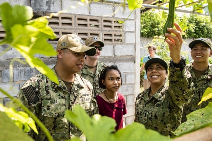 Lt. j.g. Jasmin Nicasio, from San Diego, reaches for a vegetable in the Child Protection and Development Center garden during a community service project in Chonburi.