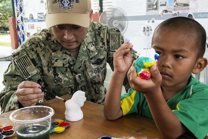 Lt. Danny Cho, from Marina, Calif., paints with a child during a community service project at the Child Protection and Development Center in Chonburi.