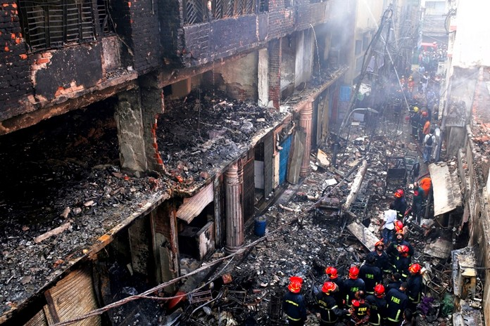 Locals and firefighters gather around buildings that caught fire late Wednesday in Dhaka, Bangladesh, Thursday, Feb. 21. (AP Photo/Rehman Asad)