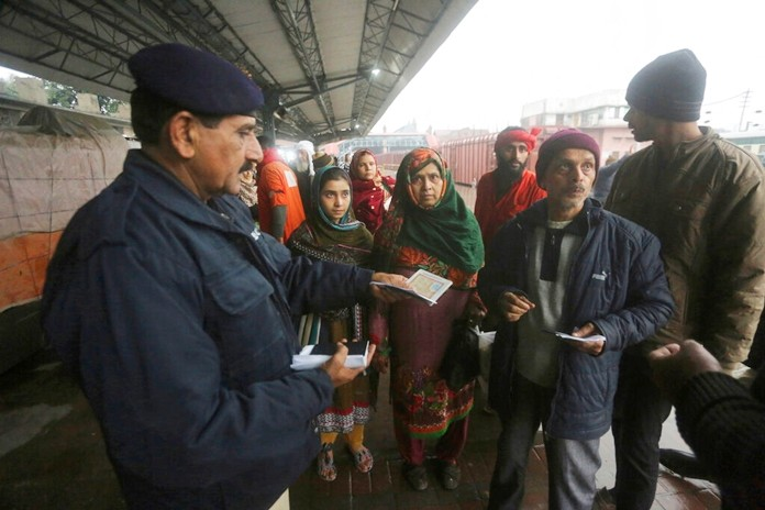 A Pakistani police officer checks documents of passengers traveling to India at Lahore railway station in Pakistan, Thursday, Feb. 21. (AP Photo/K.M. Chaudary)