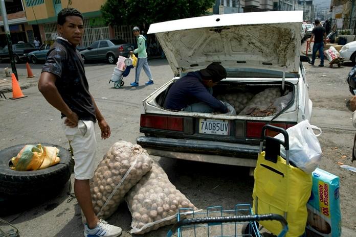A man loads his car with potatoes bought in Colombia, in San Antonio del Tachira, Venezuela, on the border with Colombia, Thursday, Feb. 21. (AP Photo/Rodrigo Abd)