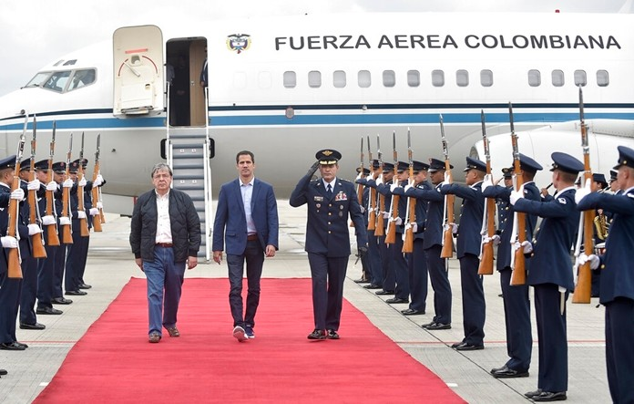 Venezuelan opposition leader Juan Guaido, who declared himself interim president of Venezuela, is escorted by Air Force Gen. Luis Carlos Cordoba, right, and Colombian Foreign Minister Carlos Holmes Trujillo during a welcome ceremony for him at the military airport in Bogota, Colombia, Sunday, Feb. 24, 2019. (Efrain Herrera/Colombian presidential press office via AP)