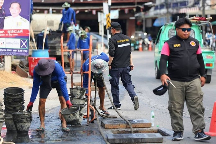 Prison inmates continued their work to scrape out clogged sewers at Sawang Pruktaram Temple, on Soi Buakhao and Third Road.