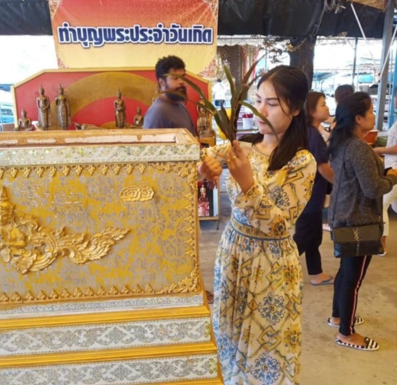 A woman makes merit by donating towards the purchase of a coffin for families who cannot afford one for their deceased relatives, at Wat Huay Yai.