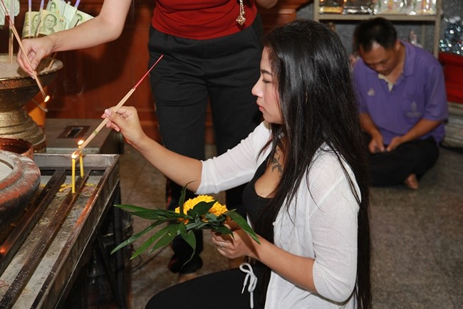 People light candles and incense to pay respect to the triple gem at Wat Chaimongkol Royal Temple.