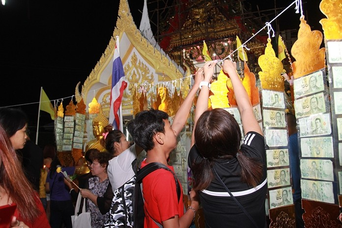 People take part in the sky robe offering ceremony at Wat Chaimongkol.