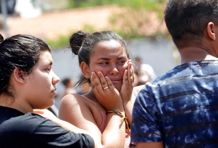 A student cries outside the Raul Brasil State School in Suzano, the greater Sao Paulo area, Brazil, Wednesday, March 13. (AP Photo/Andre Penner)