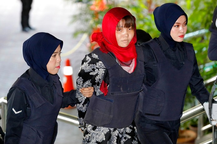 Vietnamese Doan Thi Huong, center, is escorted by police as she arrives at Shah Alam High Court in Shah Alam, Malaysia, Thursday, March 14. (AP Photo/Vincent Thian)