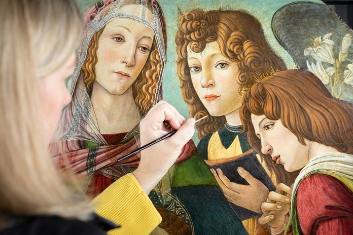 """English Heritage Conservator Rachel Turnbull completes the conservation of """"Madonna of the Pomegranate"""", a painting revealed as a rare example by the workshop of Sandro Botticelli in Florence. (Christopher Ison/English Heritage via AP)"""