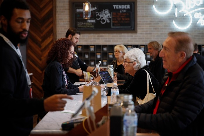 In this Feb. 19, 2019 photo, a group of seniors from Laguna Woods Village consult with sales associates at Bud and Bloom cannabis dispensary in Santa Ana, Calif. The seniors boarded a bus for the pot shop and spent hours choosing from a variety of cannabis-infused products, including candies, drinks and weed. (AP Photo/Jae C. Hong)