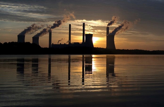 In this June, 3, 2017, file photo, the sun sets behind Georgia Power's coal-fired Plant Scherer, one of the nation's top carbon dioxide emitters, in Juliette, Ga. As climate change becomes a hotter topic in American classrooms in 2019, some politicians are pushing back against the scientific consensus that global warming is real and man-made. (AP Photo/Branden Camp, File)