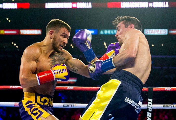 Vasiliy Lomachenko, left, from Ukraine, hits Anthony Crolla, from Britain, during a WBA and WBO lightweight title boxing bout Friday, April 12, 2019, in Los Angeles. (AP Photo/Damian Dovarganes)