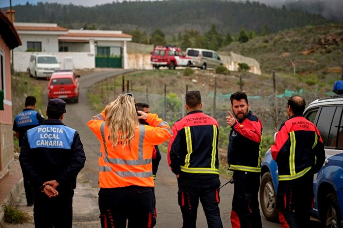 Members of an emergency team stand on a road leading to a cave at the base of the Teide volcano, where a mother and son were found in Santa Cruz de Tenerife in the Canary Islands, Spain, Wednesday, April 24, 2019. (AP Photo/Andres Gutierrez)