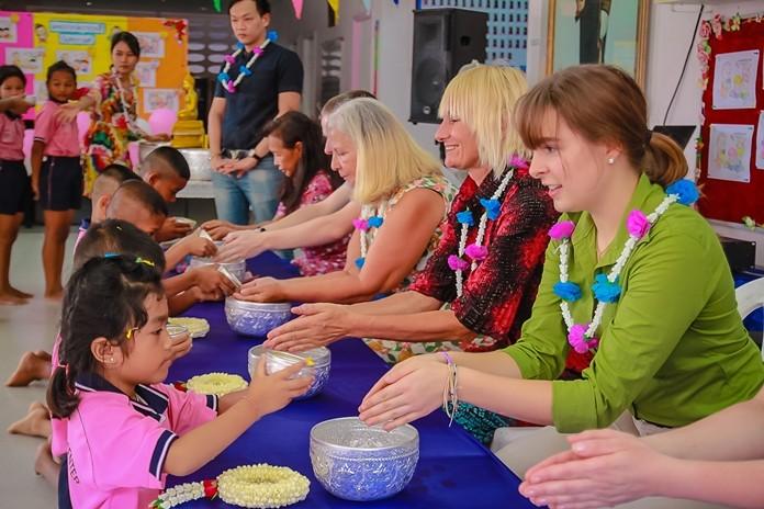Drop-In Center children pour water on the hands of volunteers.
