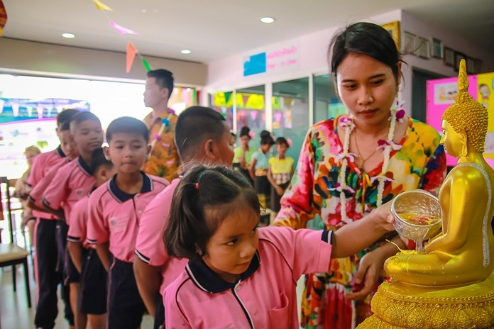 Youngster learn early about the solemn Songkran Buddha image bathing rites tradition.