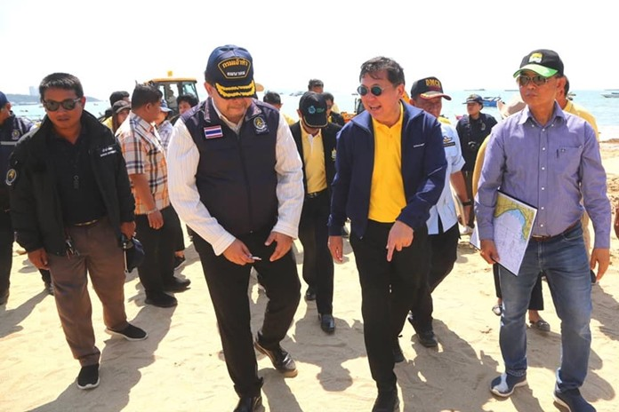 Jatuporn Buruspat (2nd right, pointing at sand), director-general of the Department of Marine and Coastal Resources, tours Pattaya Beach to witness the damage caused by the city's poor flood management.