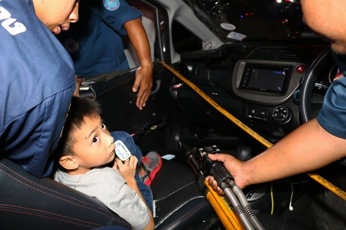 Rescue workers use specialist equipment to extricate 6-year-old Nong Namo whose broken leg was trapped against the door.