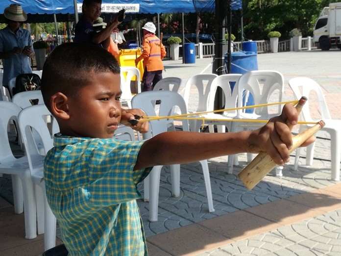 A young sharpshooter takes aim in the slingshot competition.