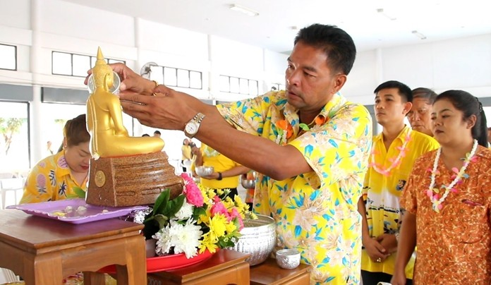 Nong Plalai Mayor Pinyo Homklin performs the Buddha image bathing rites before pouring water onto the hands of respected senior citizens.