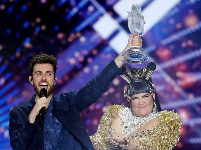 """Duncan Laurence of the Netherlands (left) celebrates with the trophy after winning the 2019 Eurovision Song Contest grand final with the song """"Arcade"""" in Tel Aviv, Israel, Saturday, May 18. Standing right is Israeli Netta Barzilai, the winner in 2018. (AP Photo/Sebastian Scheiner)"""