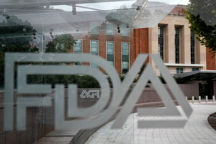 This file photo shows the U.S. Food and Drug Administration building behind FDA logos at a bus stop on the agency's campus in Silver Spring, Md. The FDA said Thursday, May 2, 2019, that a type of breast implant linked to a rare form of cancer will be allowed to stay on the market. (AP Photo/Jacquelyn Martin, File)