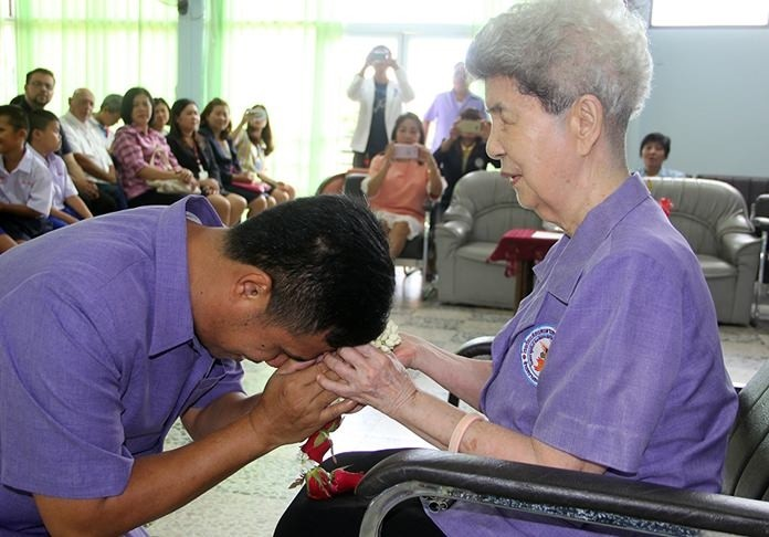 Khun Aurora received a garland from the new head teacher on her retirement.