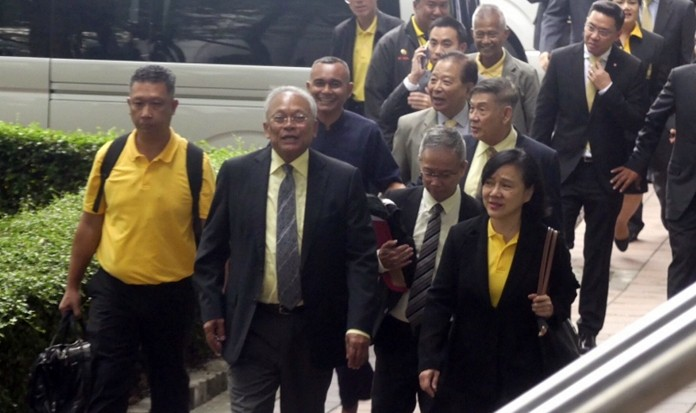 Suthep Thaugsuban and members of the now-defunct People's Democratic Reform Committee arrive at the Criminal Court in Bangkok, Tuesday, May 14.