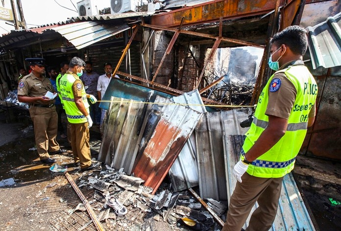 Sri Lankan security officers inspect vandalized shops owned by Muslims in Minuwangoda, a suburb of Colombo, Sri Lanka, Tuesday, May 14, 2019. (AP Photo/Chamila Karunarathne)