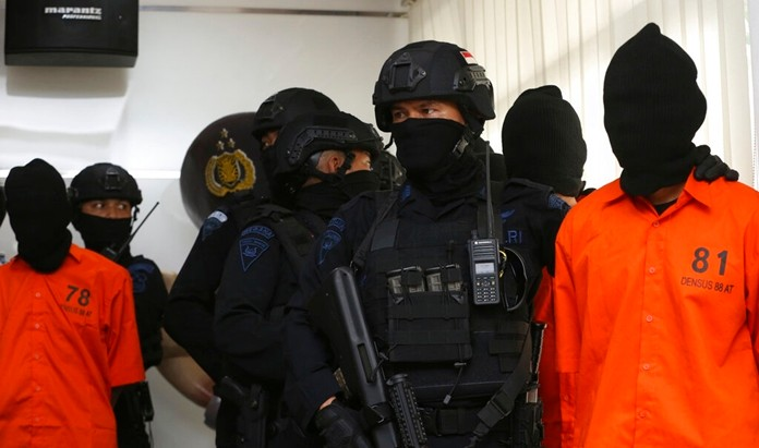 Indonesian Special Detachment 88 anti-terror police escort terror suspects during a press conference in Jakarta, Indonesia, Friday, May 17, 2019. (AP Photo/Achmad Ibrahim)