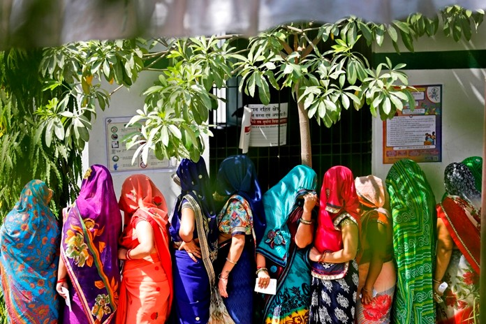 Indian women stand in queues to cast their votes in the seventh and final phase of national elections, on the outskirts of Varanasi, India, Sunday, May 19, 2019. (AP Photo/Rajesh Kumar Singh)