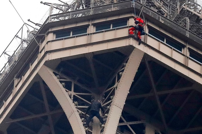 A rescue worker, top in red, hangs from the Eiffel Tower while a climber is seen below him between two iron columns Monday, May 20, 2019 in Paris. (AP Photo/Michel Euler)