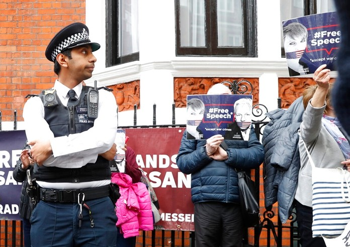A British police officer stands guard outside the Ecuadorian Embassy as protesters in support of Wikileaks founder Julian Assange demonstrate outside the embassy in London, Monday, May 20, 2019. (AP Photo/Alastair Grant)