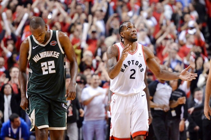Toronto Raptors forward Kawhi Leonard (2) reacts as Milwaukee Bucks forward Khris Middleton (22) looks on following the Raptors win in Game 3 of the NBA basketball playoffs Eastern Conference finals in Toronto on Sunday, May 19, 2019. (Nathan Denette/The Canadian Press via AP)