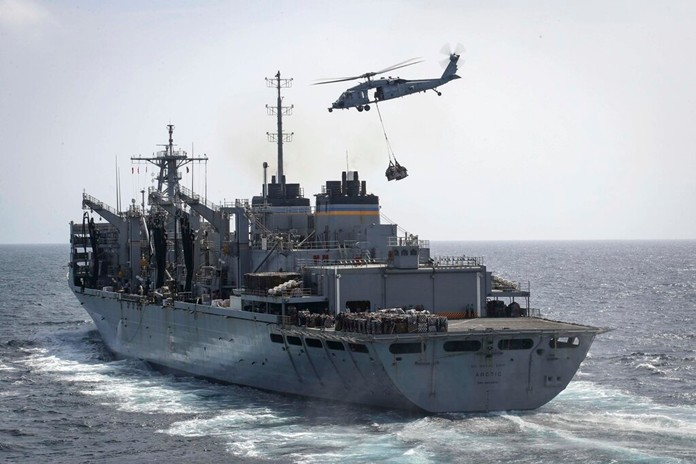 "In this Sunday, May 19, 2019, photo, an MH-60S Sea Hawk helicopter from the ""Nightdippers"" of Helicopter Sea Combat Squadron 5 transports cargo from the fast combat support ship USNS Arctic to the Nimitz-class aircraft carrier USS Abraham Lincoln during a replenishment-at-sea in the Arabian Sea.(Mass Communication Specialist 3rd Class Jeff Sherman/U.S. Navy via AP)"