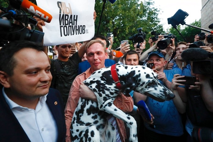 Prominent Russian investigative journalist Ivan Golunov carries his dog as he leaves an Investigative Committee building in Moscow, Russia, Tuesday, June 11, 2019. (AP Photo/Alexander Zemlianichenko)