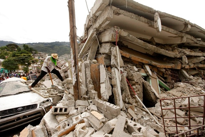 In this file photo dated Thursday, Jan. 14, 2010, people work to free trapped victims from the rubble of a collapsed building after an earthquake in Port-au-Prince, Haiti. (AP Photo/Gerald Herbert)